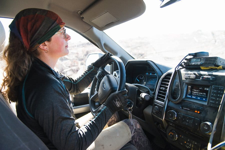 A crew vehicle operator sits in the drivers seat driving a big truck