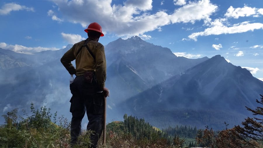 A wildland firefighter surveys the landscape and Mount Currie with smokey skies