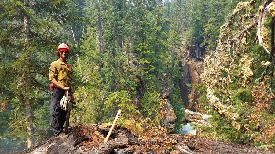 A Wildland fire fighter power saw operator stands on lookout